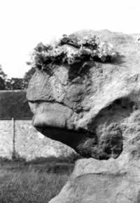 Prominent stone head in the Avebury circle decorated with flower wreath made by June Peel